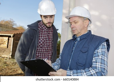 mature contractor checking his clipboard while talking to co-worker