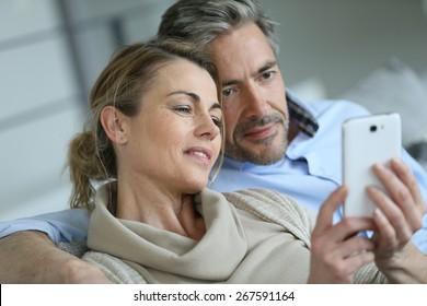 Mature coupel sittign in sofa and using smartphone
