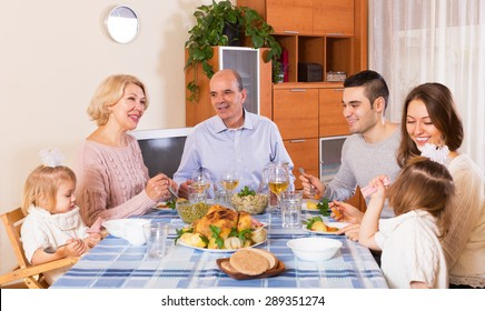 Mature couple with adult kids and grandchildren having meal together