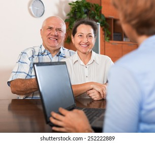 Mature couple answer questions of agent with notebook in  office