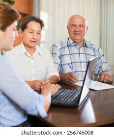 Mature couple answer questions of agent  with laptop in home