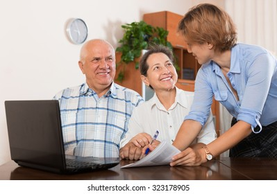 Mature couple answer questions of outreach worker with laptop in office