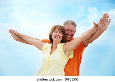 Mature couple with arms outstretched over a blue sky background