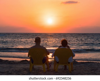 Mature couple at the beach with beach chairs in the sunset