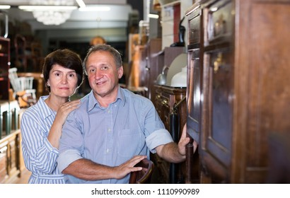 Mature couple is buying antique cupboard in store.