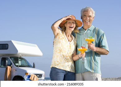 Mature couple with cocktails by motor home on beach, smiling, portrait, low angle view