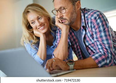 Mature couple connected with laptop at home