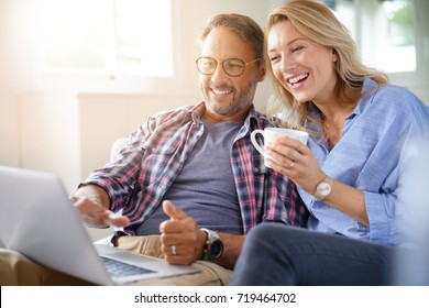 Mature couple connected on internet with laptop