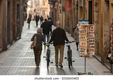 Mature couple of cyclist travelers strolling through European picturesque city.