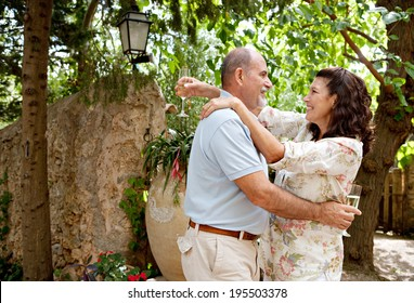 Mature couple dancing while drinking champagne in a luxury hotel garden on a summer holiday and dancing together holding their glasses. Senior people enjoying life and retirement, outdoors lifestyle.