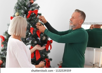 Mature couple decorating Christmas tree together at home