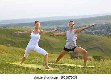 Mature couple doing Warrior 2 pose practicing yoga on top of grassy hill in countryside. Middle aged female instructor teaching male yogi to do Virabhadrasana 2 during yoga practice in nature