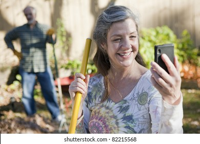 Mature couple doing yard work and on the cell phone