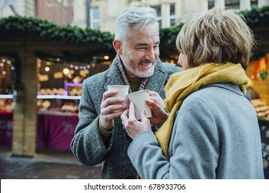 Mature couple are drinking hot drinks in a town christmas market. They are toasting the disposable cups.