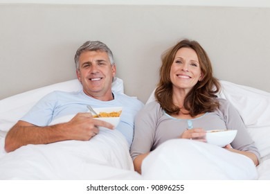 Mature couple eating cereals in bed
