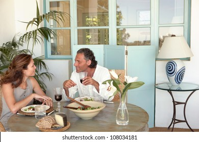 Mature couple eating and drinking together at garden table, while having a lively conversation.
