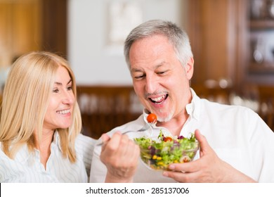 Mature couple eating a salad in the living room. Shallow depth of field, focus on the man