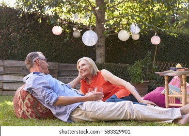 Mature Couple Enjoying Drinks In Backyard Together