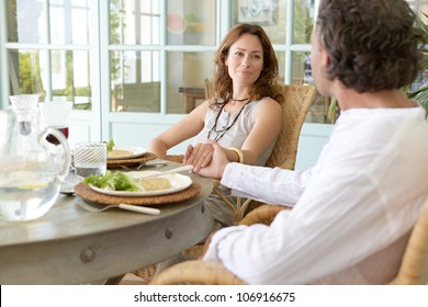 Mature couple enjoying lunch in a hotel terrace, holding hands.