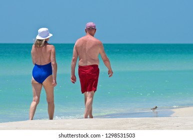 Mature Couple Enjoying a Walk on the Beach on a Beautiful Sunny Day in Florida