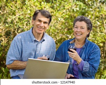 Mature couple exploring their retirement options on their laptop and toasting to the future.