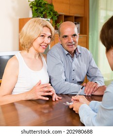 Mature couple filling questionnaire for employee at home