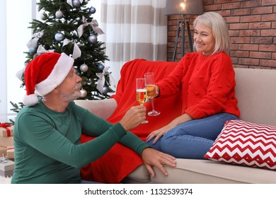 Mature couple with glasses of champagne at home. Christmas celebration