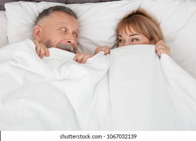 Mature couple hiding together under blanket in bed at home