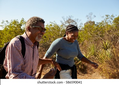 Mature Couple Hiking Outdoors In Countryside Together