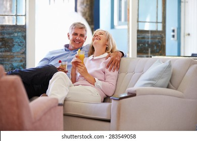 Mature Couple At Home Relaxing In Lounge With Cold Drinks