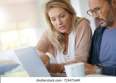Mature couple at home working on laptop computer