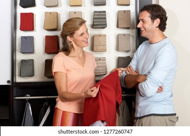 Mature couple in homeware store looking at fabric swatch display and holding textile sample