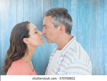Mature couple kissing against wooden plank background