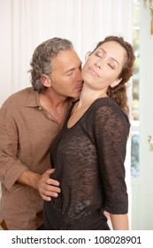Mature couple kissing while lounging at home.
