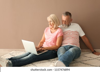 Mature couple with laptop sitting on floor in empty room. Moving into new house