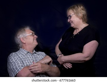 Mature couple laughing and talking together. Taken on a black background.