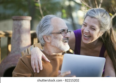 Mature couple laughing while sharing a digital tablet
