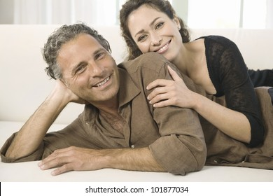Mature couple laying down on a white sofa, smiling at the camera.
