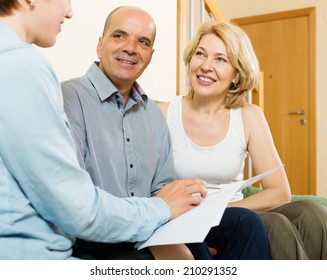 mature couple listening agent with paper or employee of the company