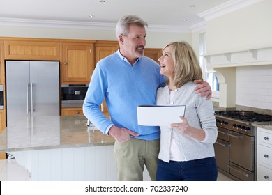 Mature Couple Looking Around Kitchen Of House For Sale
