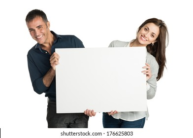 Mature Couple Looking At Camera With Sign Isolated On White Background