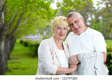Mature couple looking at camera in summer park