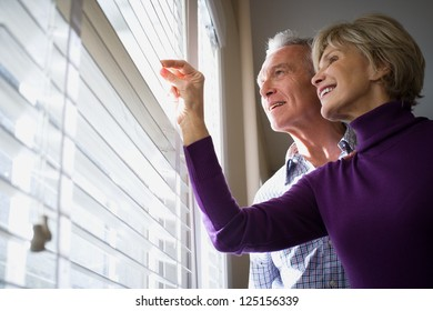 Mature couple looking through blinds