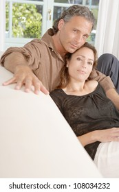 Mature couple lounging on white sofa at home.