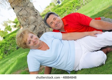 Mature couple lying on  the green lawn near the palm.