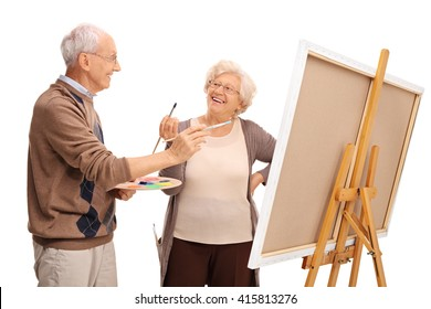 Mature couple painting on a canvas and having fun isolated on white background