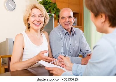 Mature couple of pensioners talking with employee at office