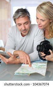 Mature couple planning vacation trip with map and laptop
