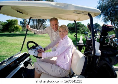 Mature couple playing golf driving buggy on course at camera