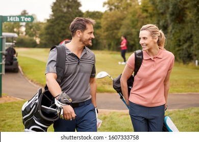 Mature Couple Playing Round Of Golf Carrying Golf Bags And Talking